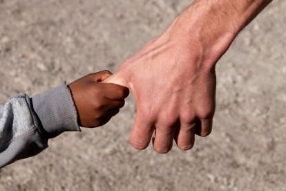 Flchtlingskind an Hand eines Helfers
